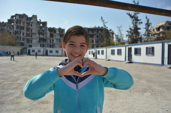 UNICEF Image: A Syrian girl stands in the grounds of a school and makes a heart shape with her hands.
