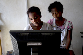 Two teenage girls work on a computer in an Internet café, Madagascar.