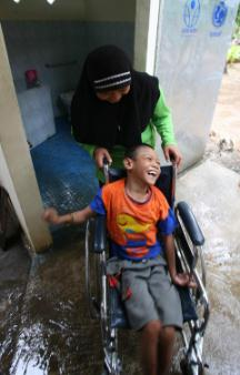 UNICEF Image: Ifran Maulana, a boy who uses a wheelchair, leaves a newly built latrine near his home in Bantul District. He is assisted by his mother. UNICEF, working with the German NGO Arche noVa, helped build 90 wheelchair accessible latrines.