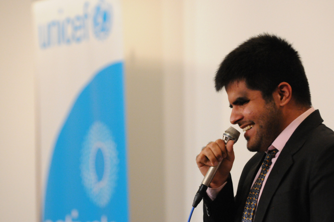 UNICEF Image: Blind young boy from India holding a mic, smiling