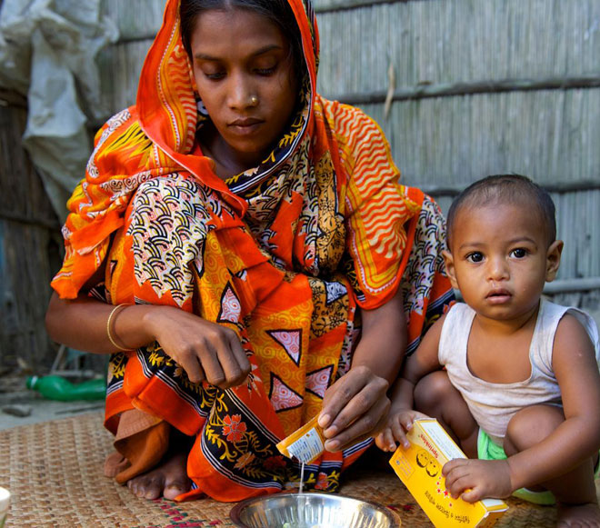 UNICEF Image: A mother adds micronutrients to her son's meal.