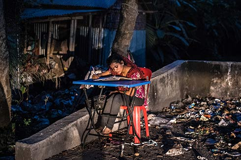 Jhuma Akhter, 14, does her homework beneath a lamppost outside her home in Khulna, Bangladesh