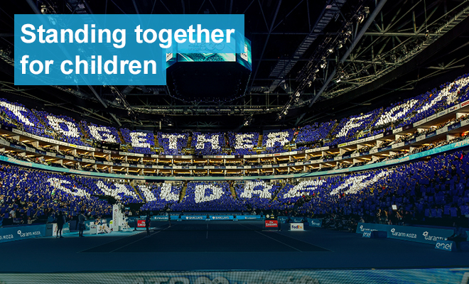 Seen from across a stadium, people in the bleachers wearing blue or white spell out the words 'together for children'