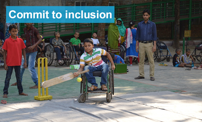 Boy in a wheelchair hits a ball with a cricket bat
