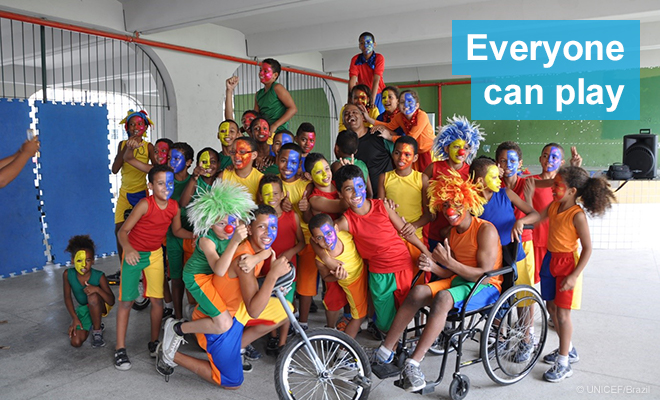 Children pose for a photo, many with facepaint and wigs; one boy is in a wheelchair