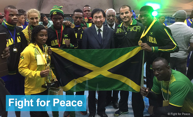 Young people hold up a Jamaican flag; some have medals or trophies