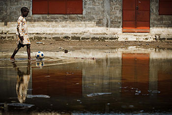 UNICEF Image: A boy kicks a football as he wades through floodwater at the A et B Hinde School in the city of Cotonou. Like many others, the school is closed due to the flooding.